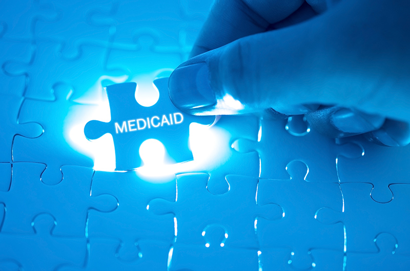 The word medicaid written on a puzzle piece being placed in the larger puzzle