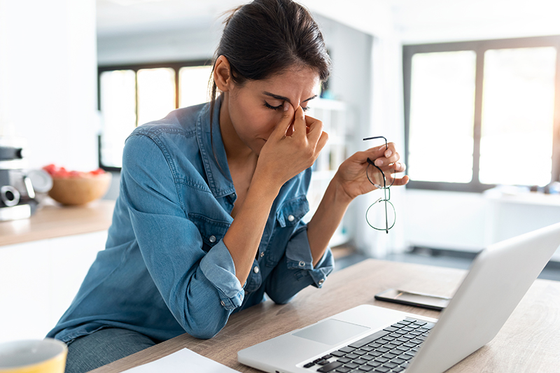 woman with headache in front of a laptop