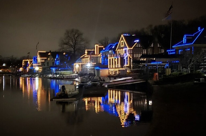 Boathouse Row lit up in blue and gold.