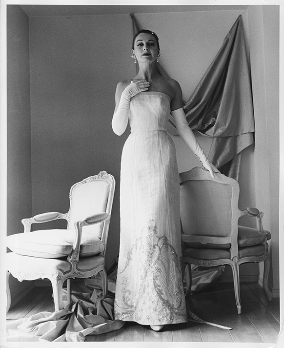 1956 promotional photograph for Galanos. A woman wears a white, beaded, strapless gown with long white opera gloves