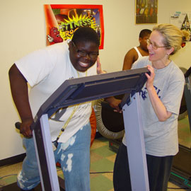 Boy on treadmill with PT trainer