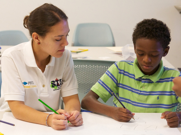 A student working with a child at Drexel's STEM Camp