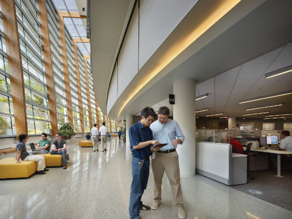 Two employees looking at mobile device in SAP lobby