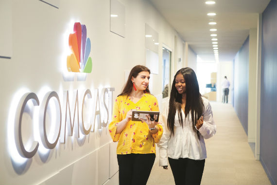 Two females walking down a hall with the comcast logo on one wall
