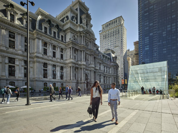Two individuals walking in the plaza in front of Philadelphia's City hall