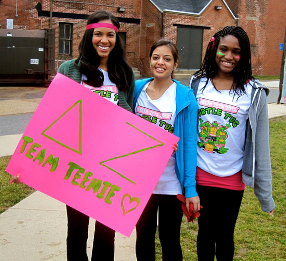 Members of Delta Zeta Sorority pose after their Turtle Tug event holding a sign that says D Z Team Teenie