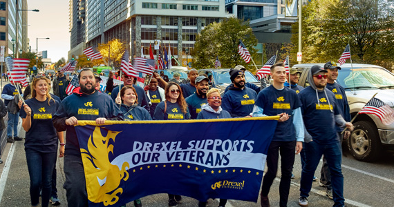 Drexel Dragons at the Veterans Parade Holding a Drexel Supports Our Veterans Banner
