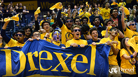 Drexel students cheer on their team at a sporting event.