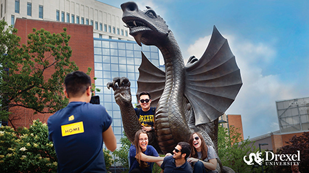 Students pose for a photo with the dragon statue.