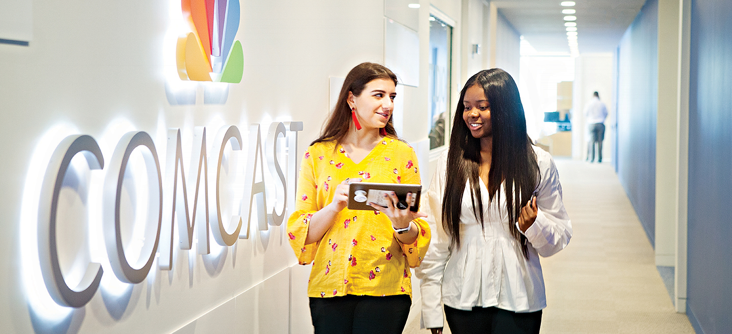 Two women look at a tablet as they walk past an illuminated Comcast sign in a corporate office.