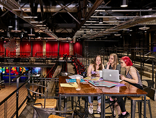 Three women seated at a table overlooking a modern performance space look at a laptop.