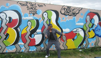 Graffiti artist Blade in front of a new graffiti piece of his name