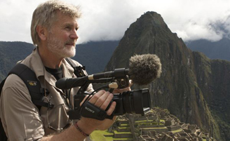photograph of Boyd Matson holding a camera with mountain in the background