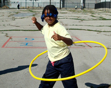 Photograph of young girl hula hooping on cracked asphalt in playground