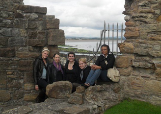 Photograph of 5 students in Edinburgh with water in the background