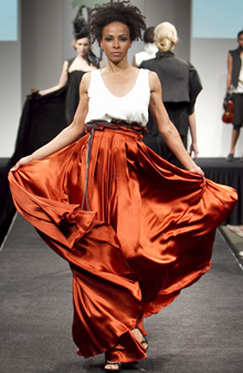 Model on runway with white and orange flowing gown on