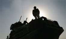 Silhouette of a soldier standing on top of a Tank