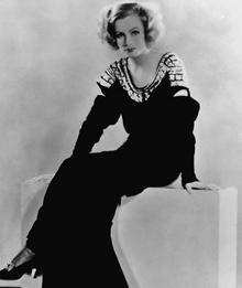 Black and White Photograph of Garbo in Black Dress and Heels sitting down