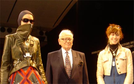 Pictured: Pierre Cardin, President of the Fashion Jury with Megan Stein and her model on the runway of the Carrousel du Louvre.