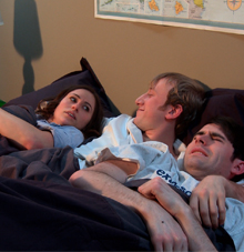 Film still from Off Campus with 3 people in a bed