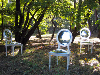 mirrored chairs surrounded by trees
