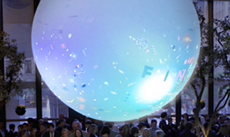 Blue lighted ball above party crowd with digital confetti